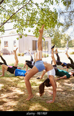 Female Instructor Leading Outdoor Yoga Class - Stock Photo