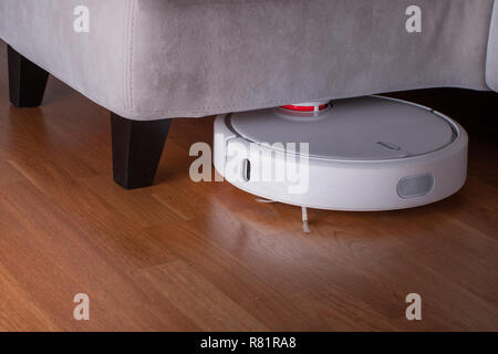 white Robot vacuum cleaner runs in corner under sofa on wood parquet floor. Modern smart cleaning technology housekeeping. - Stock Photo