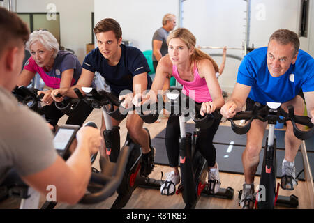 Male Trainer Taking Spin Class In Gym - Stock Photo