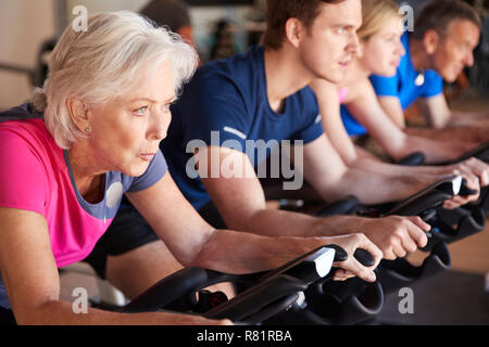 Close Up Of Group Taking Spin Class In Gym - Stock Photo