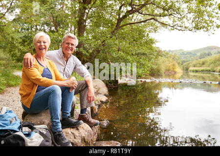 Portrait Of Senior Couple On Hike Sitting By River In UK Lake District - Stock Photo