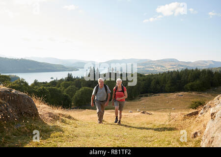 Senior Couple Climbing Hill On Hike Through Countryside In Lake District UK Together - Stock Photo