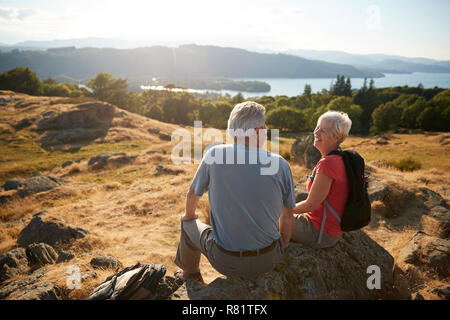 Senior Couple Resting At Top Of Hill On Hike Through Countryside In Lake District UK - Stock Photo