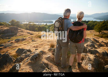 Rear View Of Senior Couple Standing At Top Of Hill On Hike Through Countryside In Lake District UK - Stock Photo