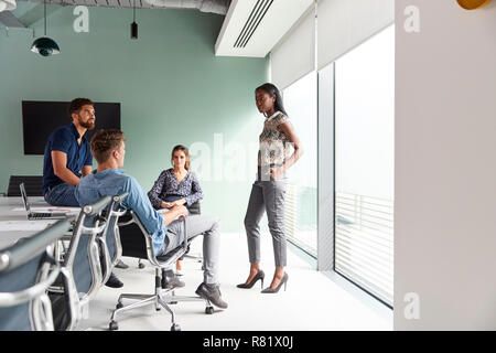 Casually Dressed Businessmen And Businesswomen Having Informal Meeting In Modern Boardroom - Stock Photo