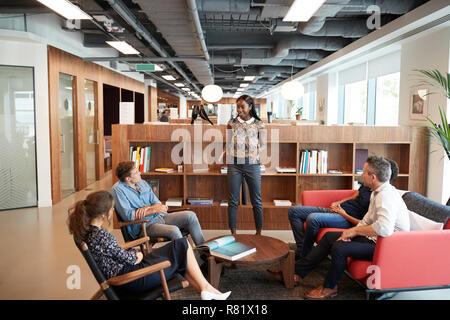 Casually Dressed Businessmen And Businesswomen Having Informal Meeting In Modern Office - Stock Photo