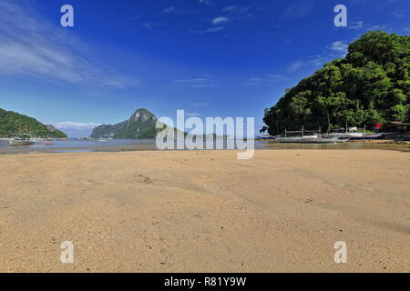 Tour and fishing boats moored and stranded at the beach of Bacuit bay at low tide in a sunny morning ready for going out to sea on their usual fishing - Stock Photo