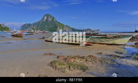 Tour and fishing boats stranded and moored at the beach of Bacuit bay at low tide in a sunny morning ready for going out to sea on their usual fishing - Stock Photo
