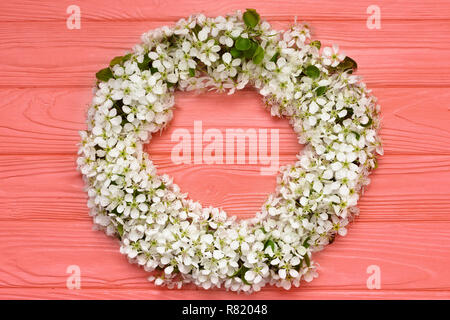 Round frame wreath made of spring flowers and leaves on coral wooden background. Flat lay. Top view. - Stock Photo