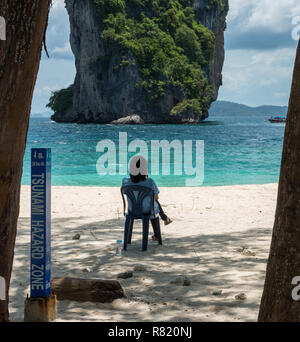 woman sitting on chair on beach in front of Sunami Hazard sign - Stock Photo