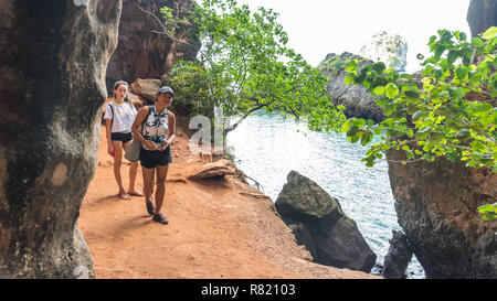 Mother and daughter in shorts walking on path next to sea - Stock Photo
