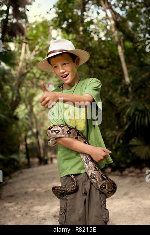 Cheerful young boy posing with a snake wrapped around his body. - Stock Photo
