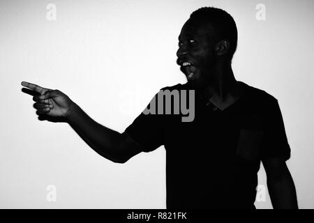 Spooky horror portrait of young African man pointing finger