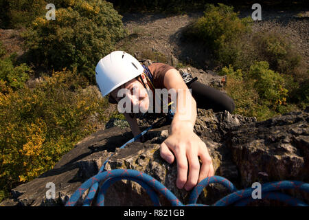Young girl rockclimbing - reaching the summit, Pikovice, Czech republic - Stock Photo