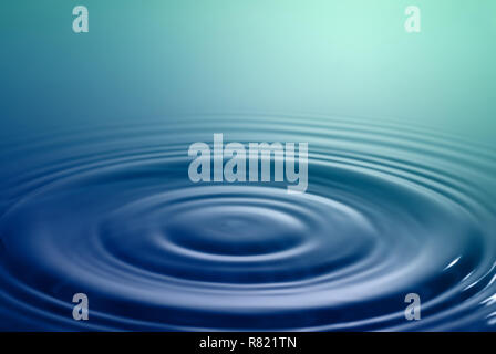 Tranquil scene. Symmetrical smooth circles and waves on water surface after splash. - Stock Photo