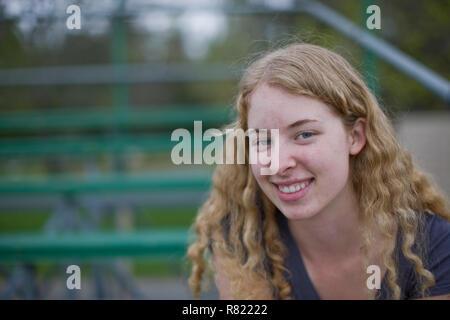 Smiling woman sitting on bleachers at sport field