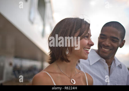 Laughing young woman standing next to her smiling partner. - Stock Photo