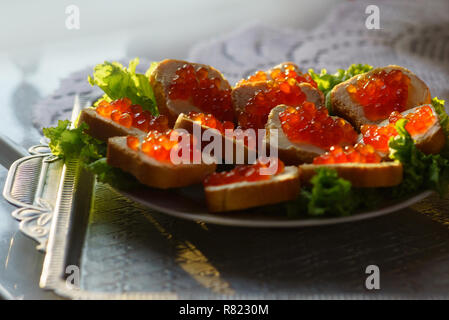 Sandwiches with red caviar on a plate. Delicious sandwiches on the festive table - Stock Photo