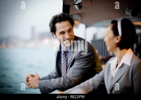Young businessman smiling at his female colleague while traveling across a harbor on a ferry. - Stock Photo