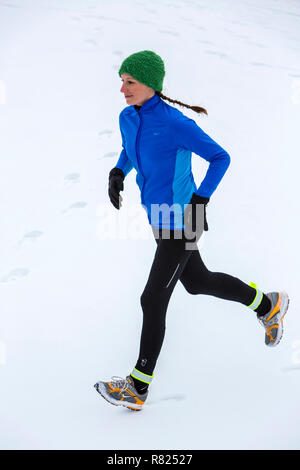 Female jogger on a run in winter in the snow - Stock Photo