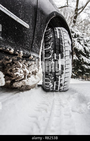 Car with winter tyres parked on a road covered with snow - Stock Photo