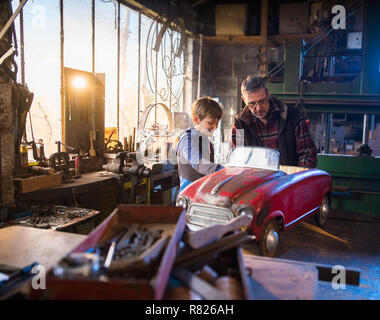 Father and his young son in a DIY workshop to repair a pedal car - Stock Photo