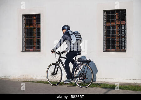 Male courier with bicycle delivering packages in city. - Stock Photo