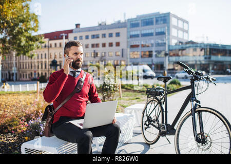 Businessman commuter with electric bicycle sitting on bench, using laptop and smartphone. - Stock Photo