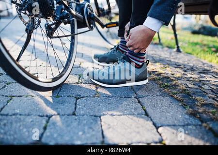 Midsection of commuter with bicycle traveling from work in city, tying shoealaces. - Stock Photo