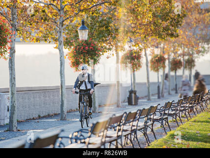 Hipster businessman commuter with bicycle traveling home from work in city. - Stock Photo