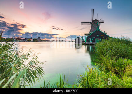 Traditional Dutch windmills near water at sunset, Zaanse Schans, Amsterdam - Stock Photo