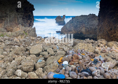 Plastic waste washed in from the sea contaminates rocks and beaches in the Caribbean - Stock Photo