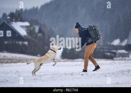 Friendship between pet owner and his dog. Young man playing with labrador retriever in winter landscape. Jizera mountains, Czech Republic