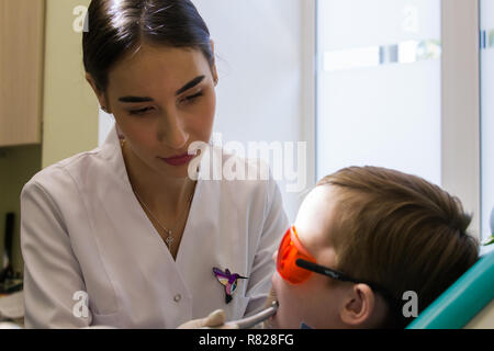 Reception at the dentistry. A young female dentist examines the oral cavity of a kid - Stock Photo