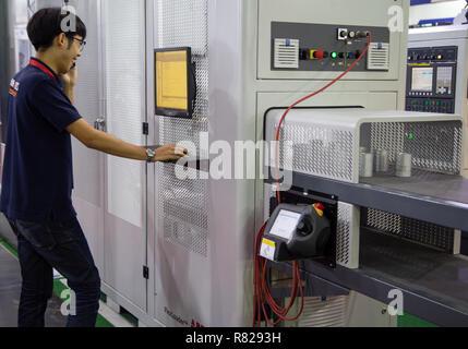 Bangkok, Thailand - November 21, 2018: Worker operate automation robotic arm flexible loader machine in Metalex 2018 - Stock Photo