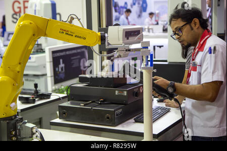Bangkok, Thailand - November 21, 2018: Worker control robot arm to loading and unloading workpiece in Metalex 2018 - Stock Photo