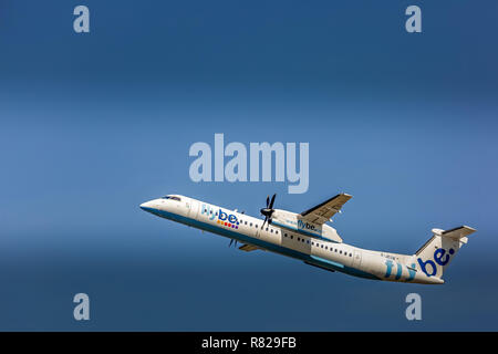 A Bombardier Dash 8 Q400 airliner, registration G-JECN, of the British Airline Flybe, taking off and heading in to a blue sky. Lots of copy space. - Stock Photo