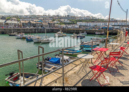 The coastal town  of Porthleven in Cornwall, England, showing small boats in the harbour and the surrounding buildings. - Stock Photo
