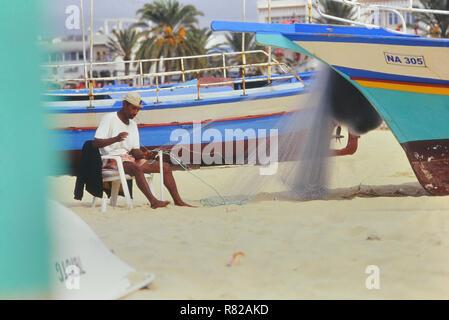Local fisherman mending his nets. Hammamet. Tunisia. North Africa - Stock Photo