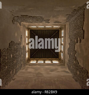 Low angle centered view on the inside of a tower of, of Nasrid Palace , with leftovers of decorative stone carvings and arch windows in the top Alhamb - Stock Photo