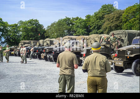 Meeting of re-enactors in American World War Two battledresses and GMC CCKW 6x6 US Army cargo trucks - Stock Photo