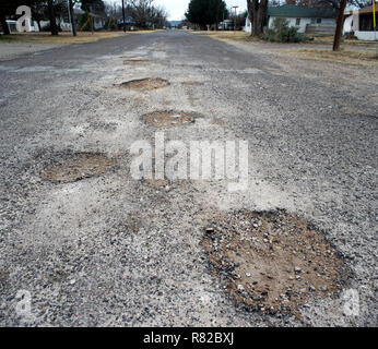 Potholes in an Alpine, Texas, street. - Stock Photo