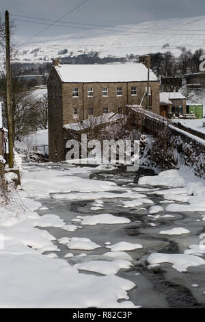 The historic Gayle Mill, Wensleydale, North Yorkshire, covered in snow. - Stock Photo