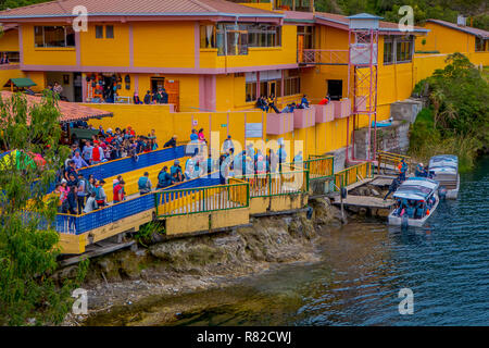 CUICOCHA, ECUADOR, NOVEMBER 06, 2018: Above view of yellow information building with some tourists boarding a boat to have a tour in the Cuicocha lake in Ecuador - Stock Photo