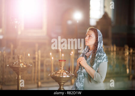 Russian beautiful Caucasian woman with red hair and a scarf on her head is in the Orthodox Church, lights a candle and prays in front of the icon. - Stock Photo