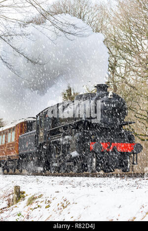 Portrait shot of vintage steam locomotive & first carriage approaching head-on in falling snow. Steam train puffing out smoke & steam from smokestack. - Stock Photo