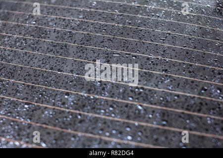 Drops of water on rear car window, heating stripes visible. - Stock Photo
