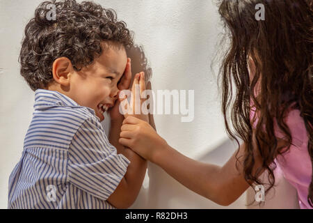 A little boy looks at his sister laughing as she grabs his arm. Playing with his older sister downtown outdoors at the community square. - Stock Photo