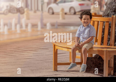 On a sunny day downtown urban city a boy sits on a round bench next to the fountains. - Stock Photo