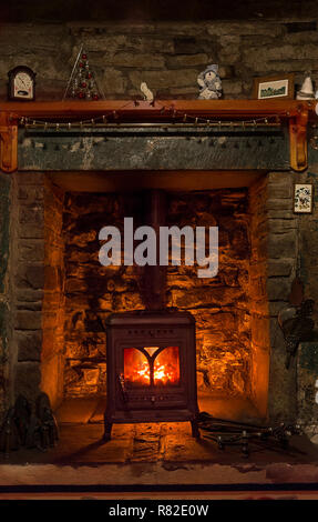 Wood burning stove in a stone fireplace - Stock Photo